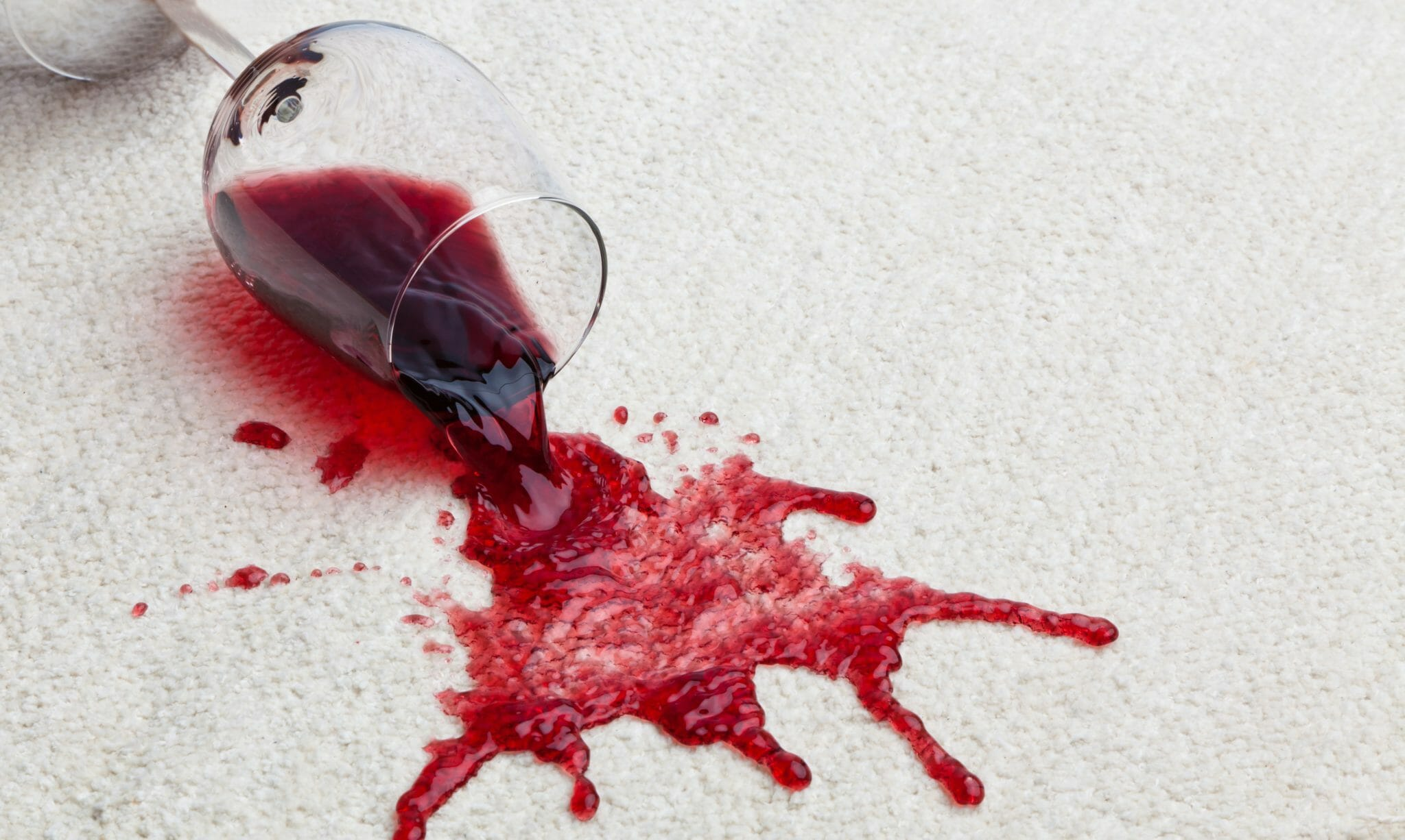 Wine glass with red wine spilling on the white carpet